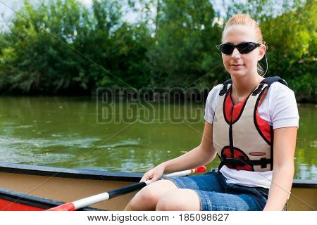 young woman canoeing on the neckar river in germany.
