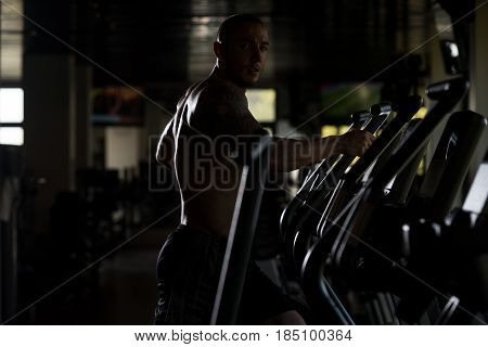 Athlete Doing Aerobics Elliptical Walker In Gym