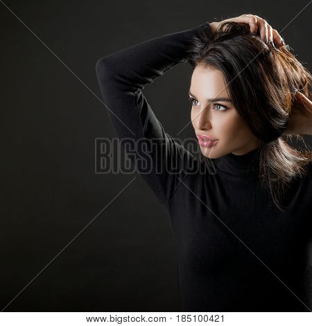 Portrait of pretty young woman. Beautiful female model posing over black background