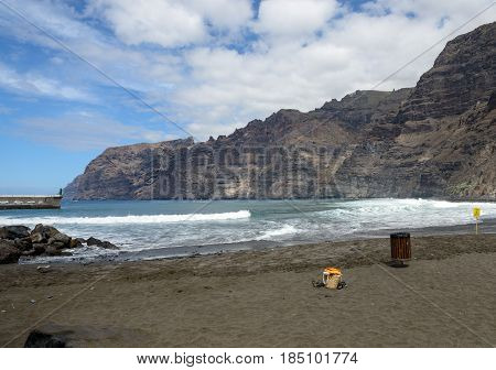 Waves in harbor of Guios beach near Los Gigantes port entrance at foot of Gigantes cliffs in the stormy day Tenerife Island Canary Islands Spain.