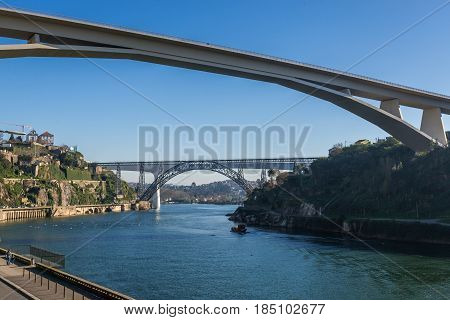 Prince Henry Bridge between cities of Porto and Vila Nova de Gaia Portugal. Old and new railway bridges on background poster