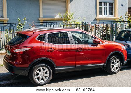 STRASBOURG FRANCE - APR 8 2017: Red Nissan Qashqai parked on street. The Nissan Qashqai is a compact crossover SUV produced by the Japanese car manufacturer Nissan since 2006.