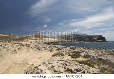 An image of a watch tower and the coastline at Dwerja Bay Gozo which is an island of the Maltese archipelago in the Mediterranean Sea.