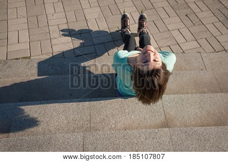 Joyful Girl Sits On The Steps In The Park, Relaxing After Roller Skating