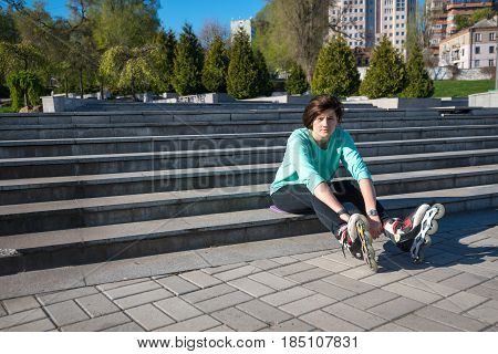 Tired Girl Sits On The Steps In The Park, Stretching Out Her Legs