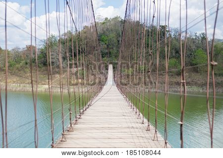 strong suspension bridge stretches through the middle of lake Kaeng Krachan tourist area in Thailand. this image for nature landscape and holiday concept