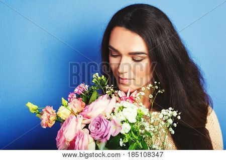Close up portrait of 35-40 year old woman with black hair, holding big bouquet of spring flowers, standing against blue background