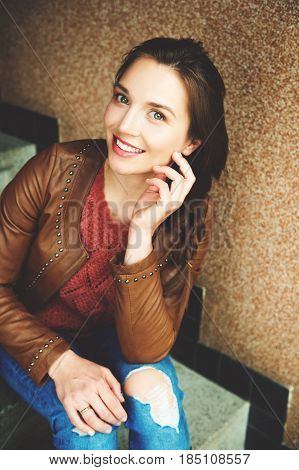 Fashion portrait of beautiful young 25-30 year old woman with professional make up, wearing brown leather jacket and ripped jeans