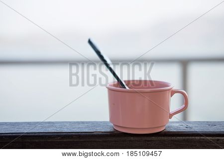 silver coffee spoon putting in pink plastic cup on wooden balcony have blur sea are background. this image for appliance concept