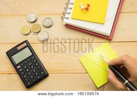 Top View. Hand Of Woman Using Pen Writing On Yellow Post-it Note And Have Black Calculator, Coin, Pi