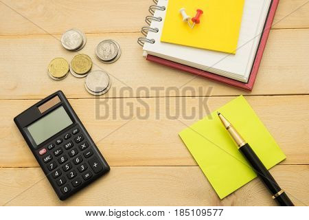Top View. Pen Putting On Yellow Post-it Note And Have Black Calculator, Coin, Pin And More Post-it N