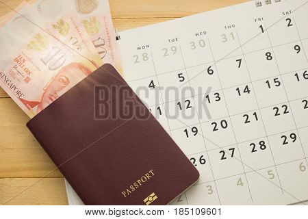 Top View. Passport Have Singapore Cash Inside Putting On Desktop Calendar Wooden Are Background. Thi