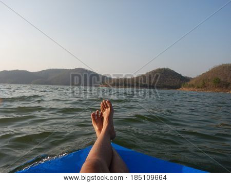 young woman sit relaxing with one's legs crossed. with big rubber pad float on water have scenery seasky and mountain are background. this image for naturetravel and seascape concept