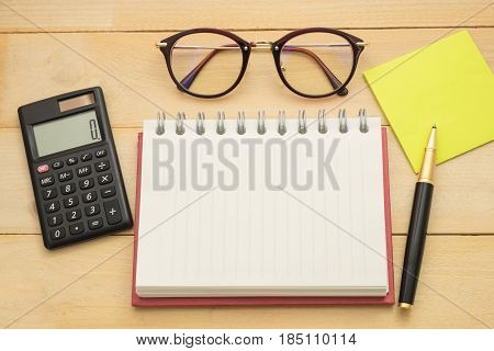 Top View. Empty Notebook, Calculator, Pust-it Note,glasses , And Ballpoint Pen All Of This Putting O