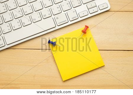 Top View. Pin Put On Top Yellow Post-it Note. Both Putting Beside Keyboard. Wooden Are Background. T