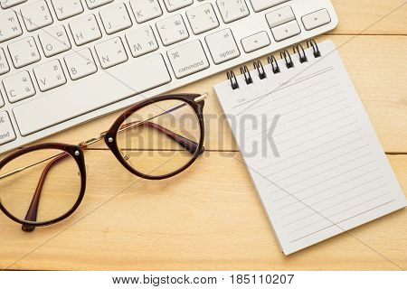 Top View. Glasses, Empty Notebook Paper And Keyboard All Of This Putting On Wooden Are Background. T
