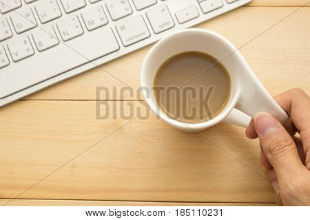 Top View. Hand Of Young Woman Holding Coffee Cup And Have Keyboard Putting Beside It. Wooden Are Bac