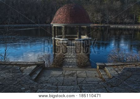 A spooky gazebo in the woods on a lake during the winter time.