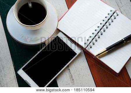 top view. white mobile phonecoffee cup with coffee pen put on top notebook paper. all putting on wooden are background. this image for businessaccessory and education concept