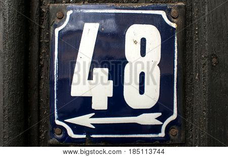 Weathered grunge square metal enameled plate of number of street address with number 48 closeup