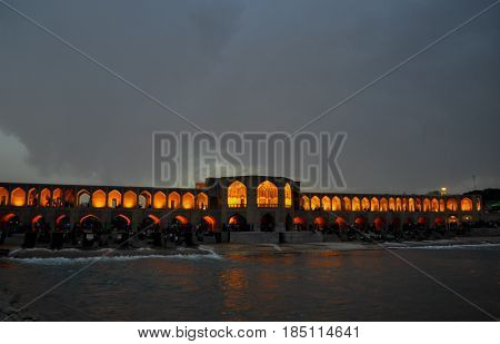 an amazing  evening shot of a bridge named Thirty-three bridges located in the Iranian city of Isfahan  with a small lake