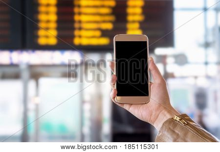 Smartphone with blank screen in bus, train, metro, subway or underground station or airport. Universal public transportation terminal. Hand holding mobile phone with free empty copy space.