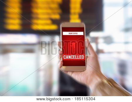 Flight cancelled. Smartphone application announces bad news to tourist. Strike or problem with plane. Woman holding mobile phone in airport terminal. Timetable and schedule in the blurred background.