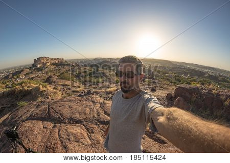 Tourist Taking Selfie In Backlight At Jodhpur Fort From Above, Perched On Top Dominating The Blue To