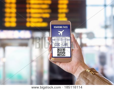Boarding pass in mobile phone. Woman holding smartphone in airport with modern ticket on screen. Easy and fast access to aeroplane. Terminal and timetable in the blurred background.