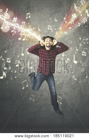 Portrait of Afro man enjoying a music on the headphone while dancing with musical notes