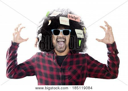 Afro man wearing sun glasses screaming with help word on sticky notes over his head isolated on white background