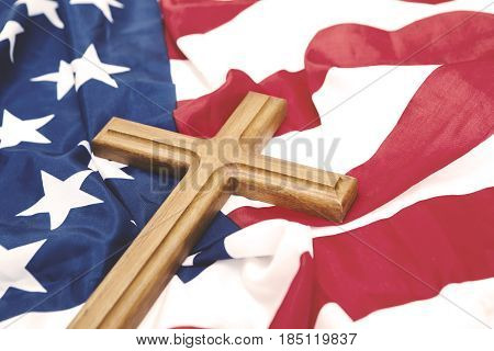 Closeup of wooden crucifix over an American flag memorial day concept