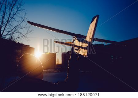 plane is on the radio control, the guy is holding the plane in his hand at sunset. Run the model airplane. Winter