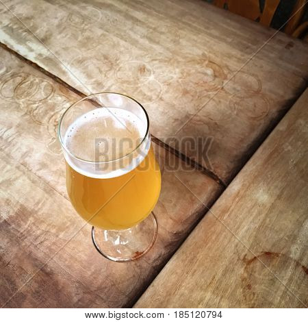 Glass of unfiltered beer on a wooden bar table.
