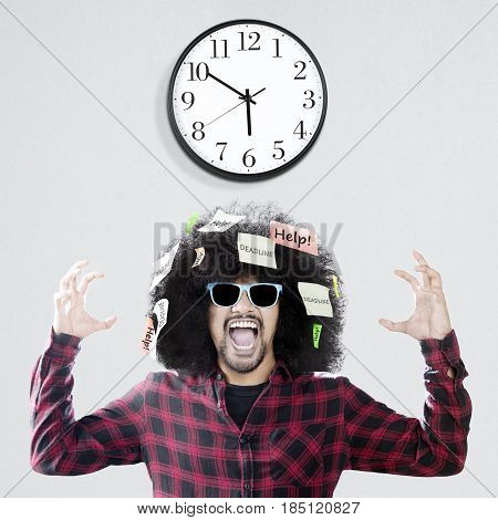 Afro man with curly hair looks anxious standing under a wall clock while screaming with Help and Deadline words attached on his hair