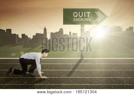 Image of Middle Eastern businessman ready to run with text of quit smoking on the signpost