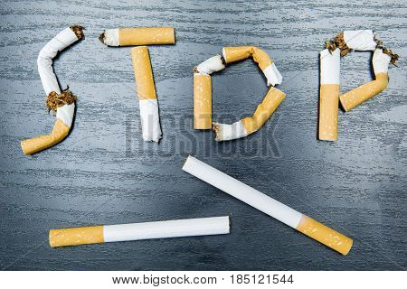 Stop smoking word written with broken cigarette on the wooden table. Concept for quitting smoking