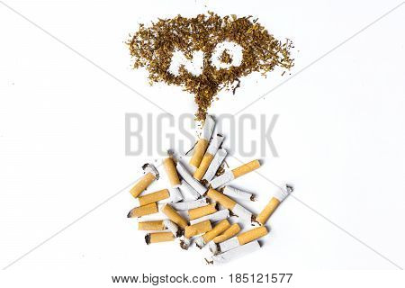Close up of broken cigarettes and no smoking sign made of tobacco isolated on white background