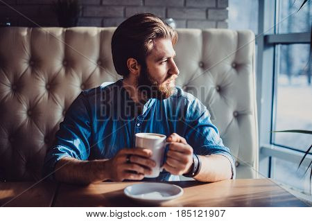 Side View Of Bearded Man Sitting By The Table Near The Window Drinking Coffee In Cafe