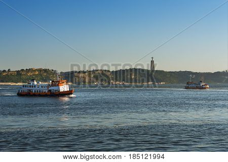 Two passenger boats (Cacilheiros) crossing the Tagus River in Lisbon Portugal with the statue of the Christ King (Cristo Rei) on the background