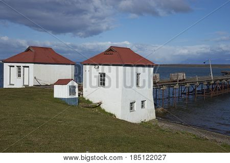PUERTO NATALES, CHILE - APRIL 10, 2017: Historic buildings and pier of a former meat refrigeration plant that have been renovated and converted into a luxury hotel.
