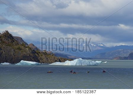TORRES DEL PAINE NATIONAL PARK, CHILE - APRIL 12, 2017: Group of people kayaking on Lago Grey in Torres del Paine National Park, near a chunk of ice from Glacier Grey.