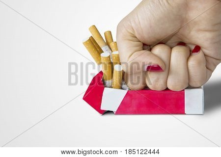 Concept of Quit smoking. Image of a female hand destroy a cigarette pack in the studio isolated on white background