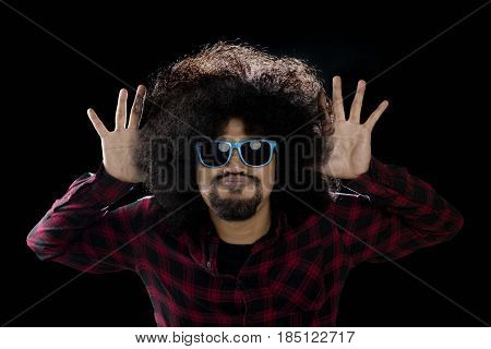 Funny afro man showing mocking gesture and silly face with dark background