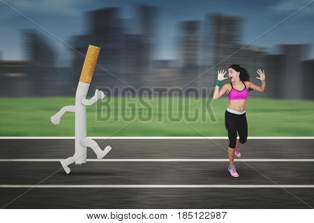 Portrait of Indian woman wearing sportswear while running away from a cigarette with a fast motion blur background