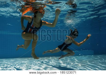 Women under water runs along the bottom of a swimming pool