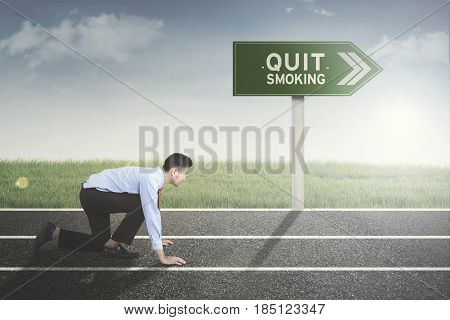 Picture of young male entrepreneur in ready position to run on the track with text of quit smoking on the signpost