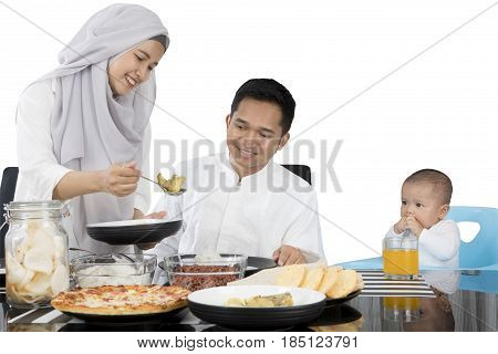 Muslim family wearing muslim clothes eating at dining table together isolated on white background
