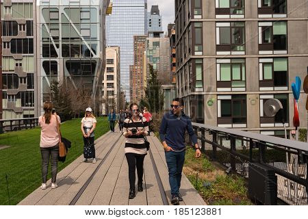 New York City -- April 12 2017 -- People strolling along the High Line built in the 1930s on an historic elevated rail line on Manhattan's West Side.
