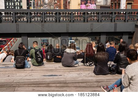 New York April 12 2017 -- People sitting down relaxing along the High Line as the traffick goes by underneath. The HIgh Line is an historic freigh rail line elevated above the streets of Manhattan's West Side.